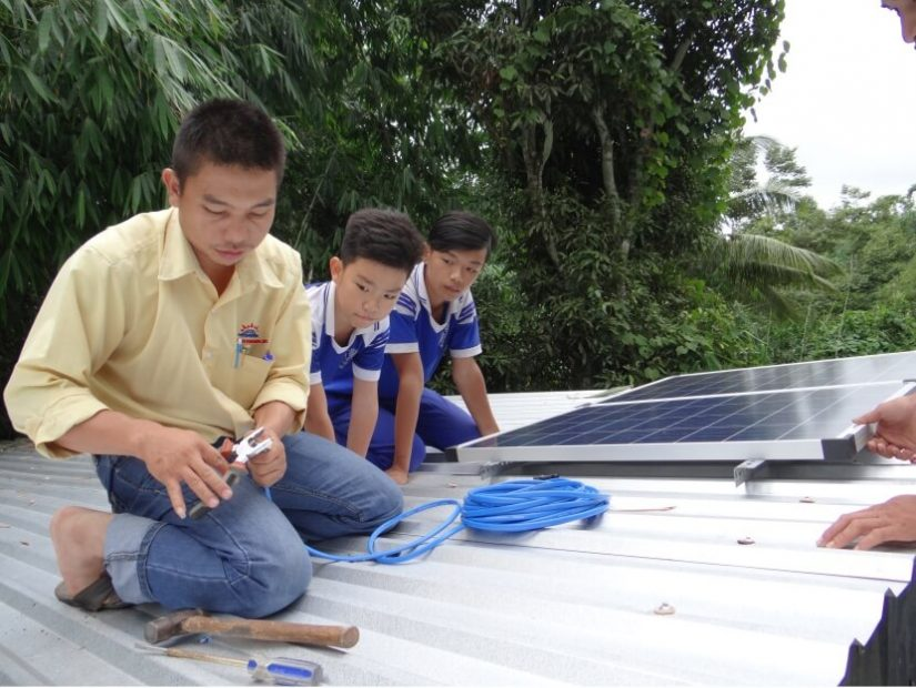 Man installing a solar panel on a roof in Vietnam. Renewables provide job opportunities and have multiple other co-benefits.